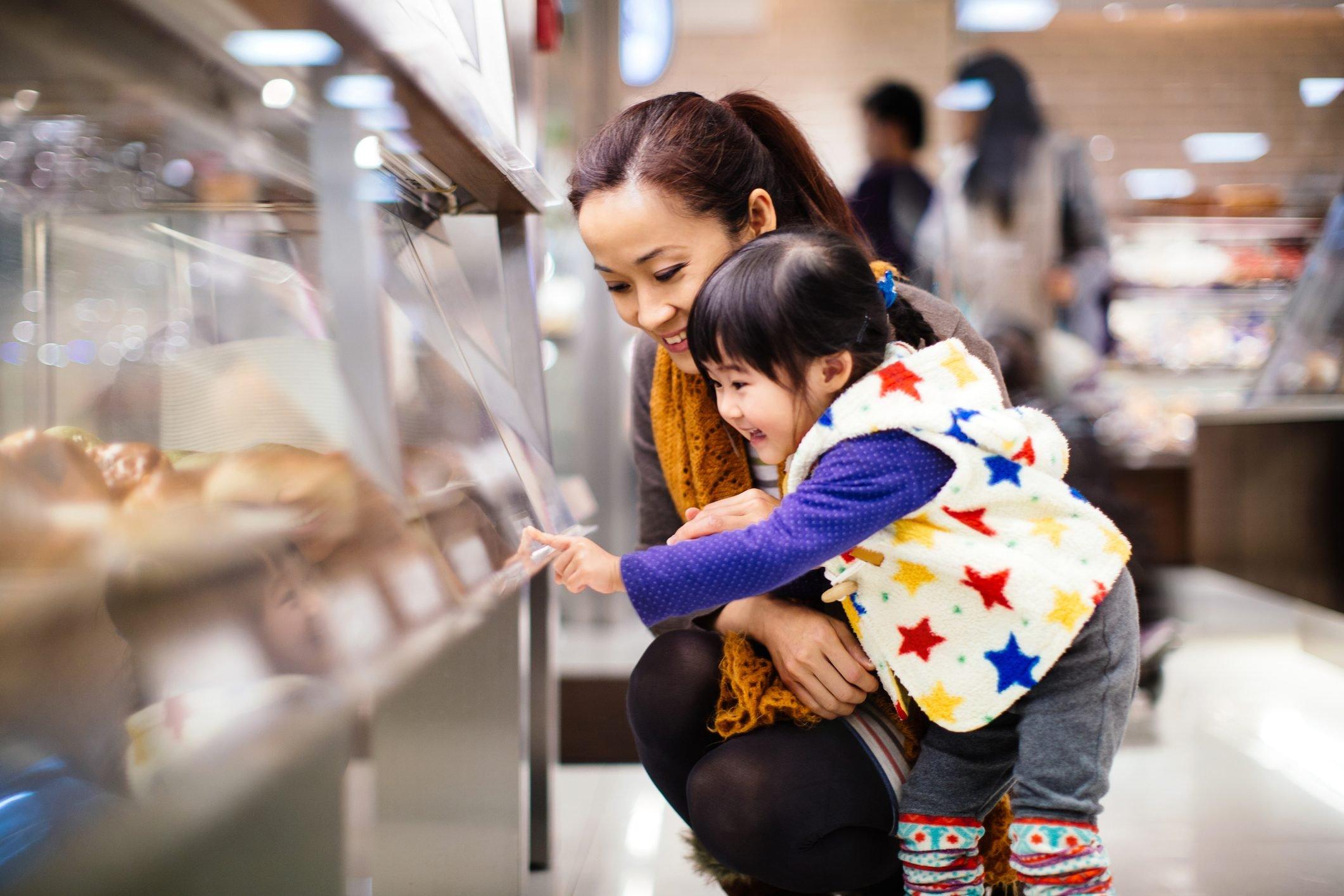 Mom & toddler girl shopping bread in the bakery
