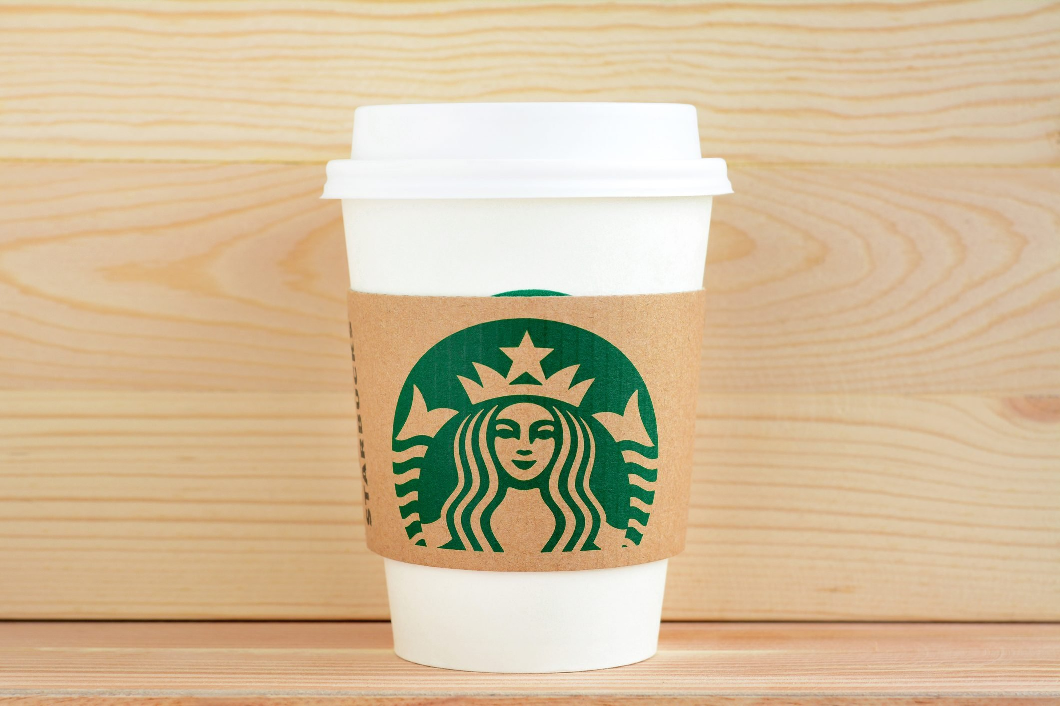 Starbucks paper coffee cup with brand logo on sleeve
