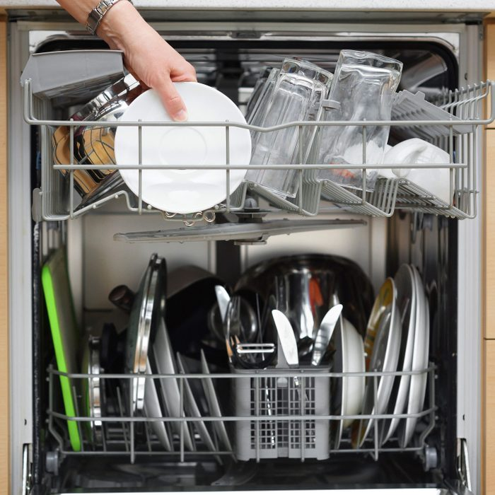 woman is using a dishwasher in a modern kitchen
