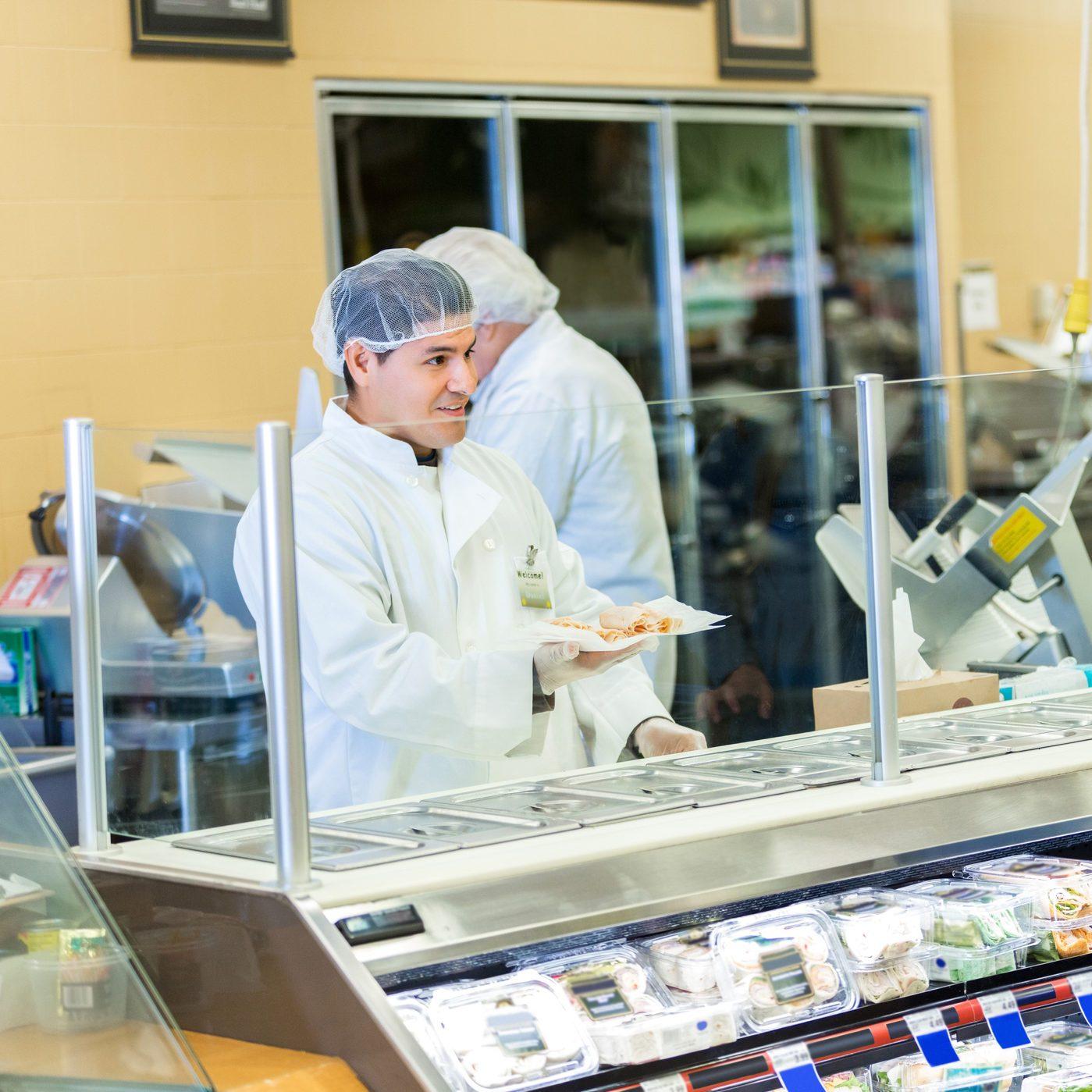 Deli employee packaging meat order for supermarket customer