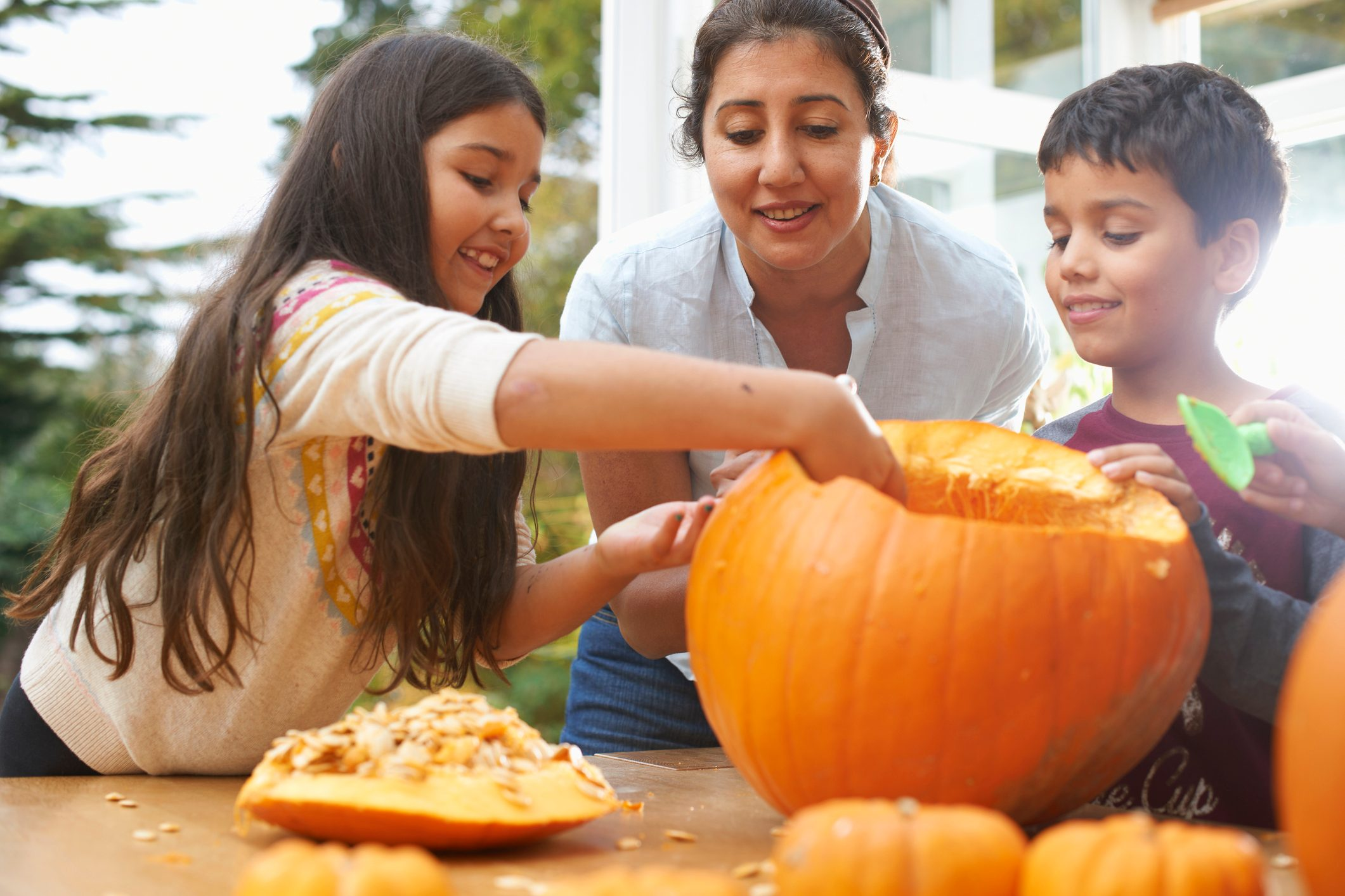Mother and children hollowing out pumpkin in dining room