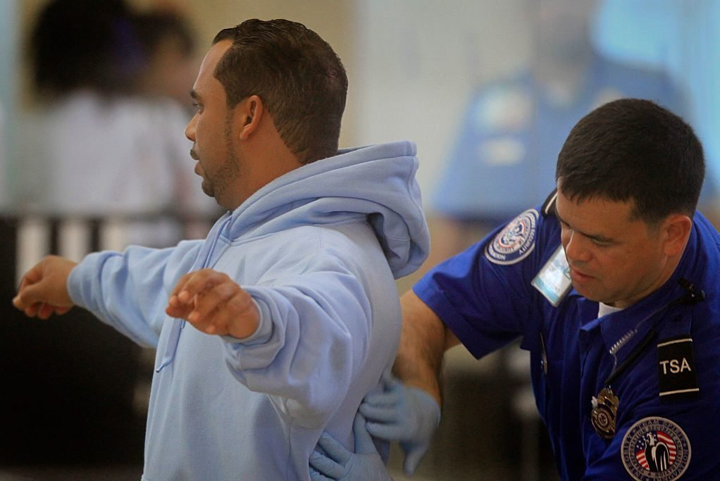 A TSA agent conducts a secondary inspection and pat–down after the traveler kept setting off the me