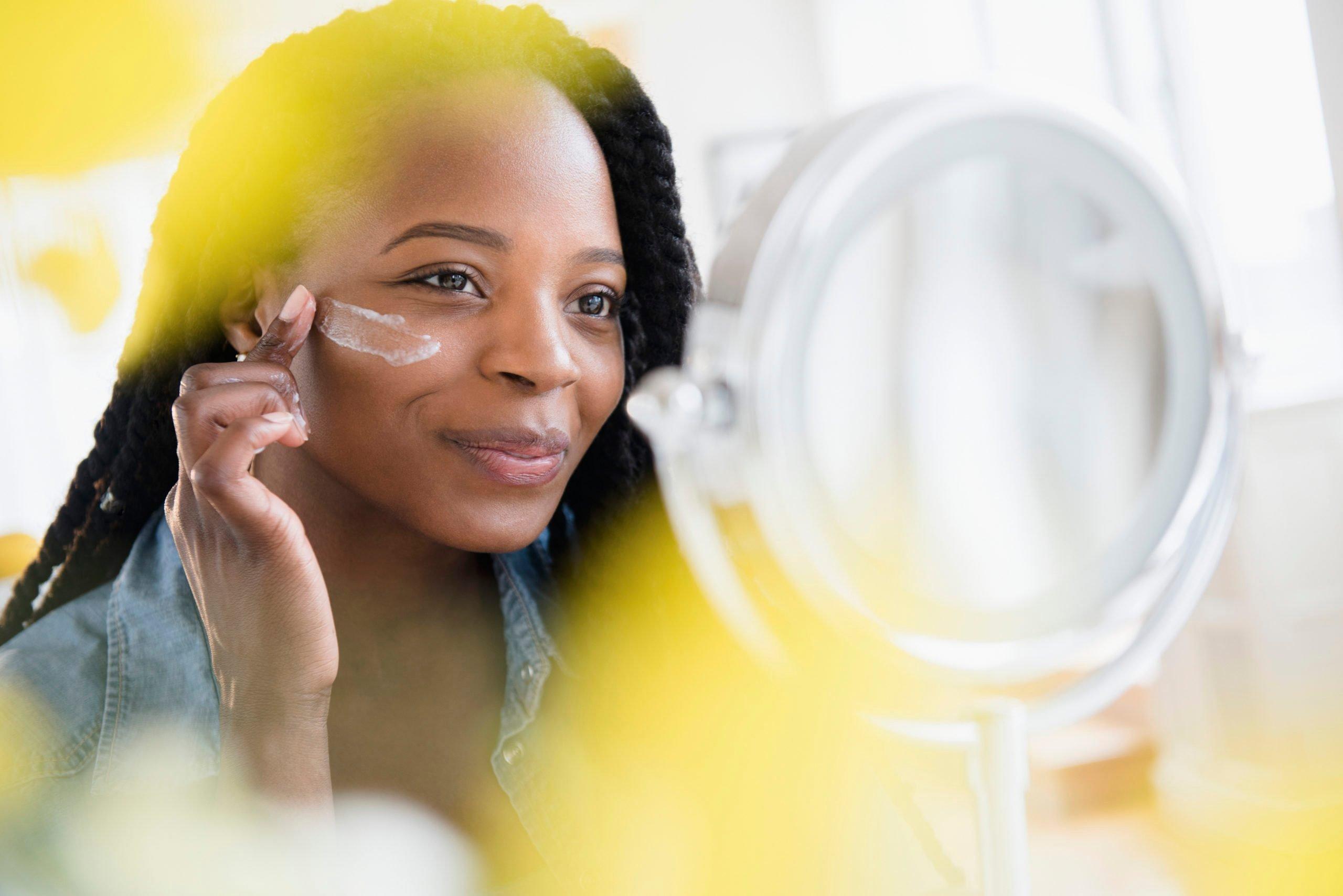 Black woman moisturizing her face