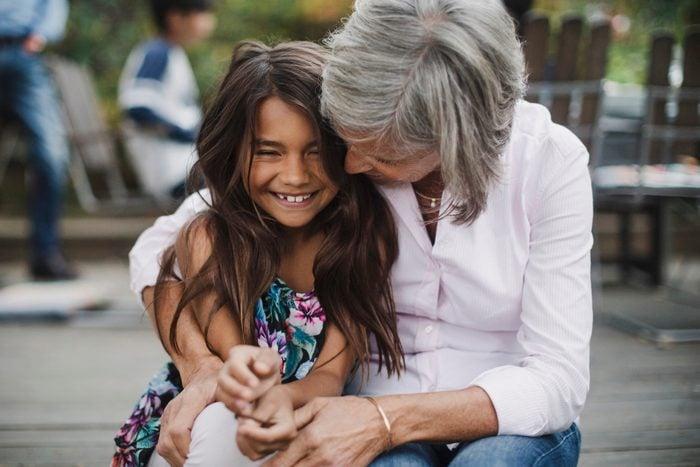Senior woman embracing granddaughter while sitting at yard