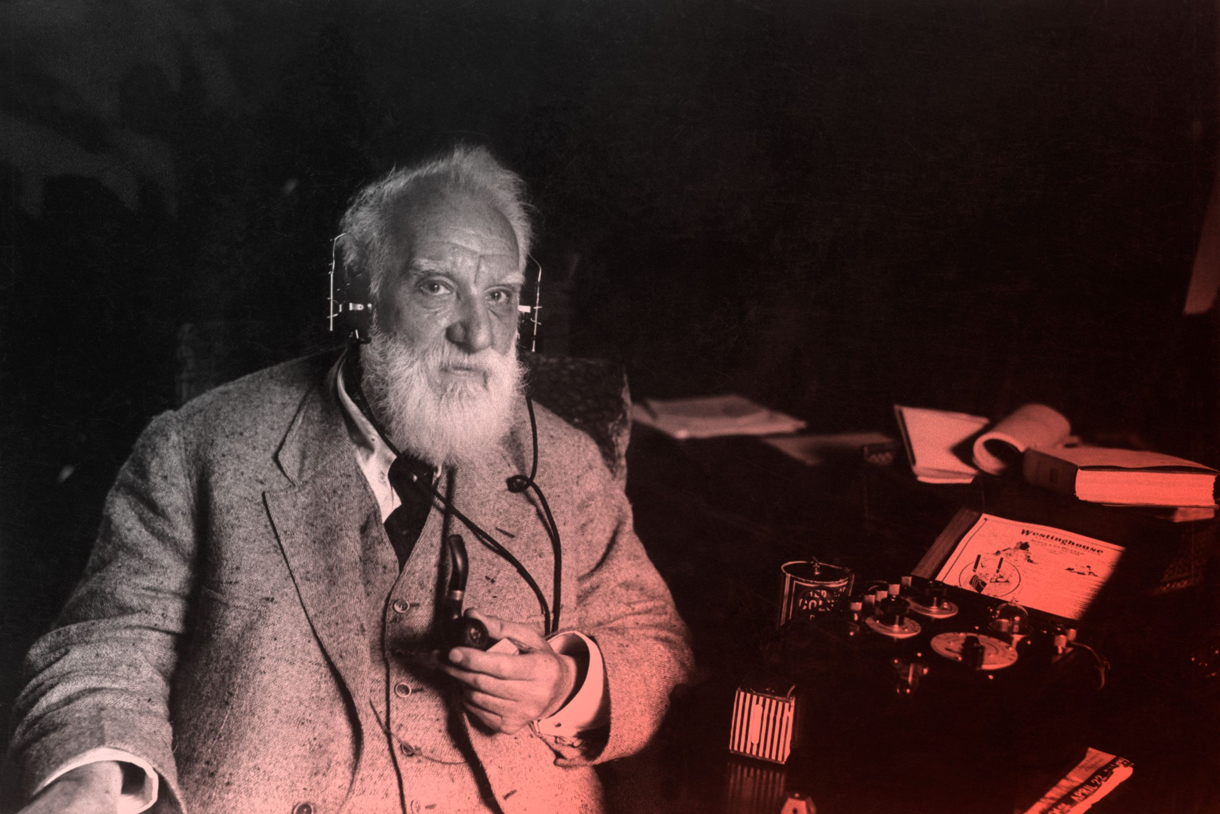 alexander graham bell sitting next to one of his inventions
