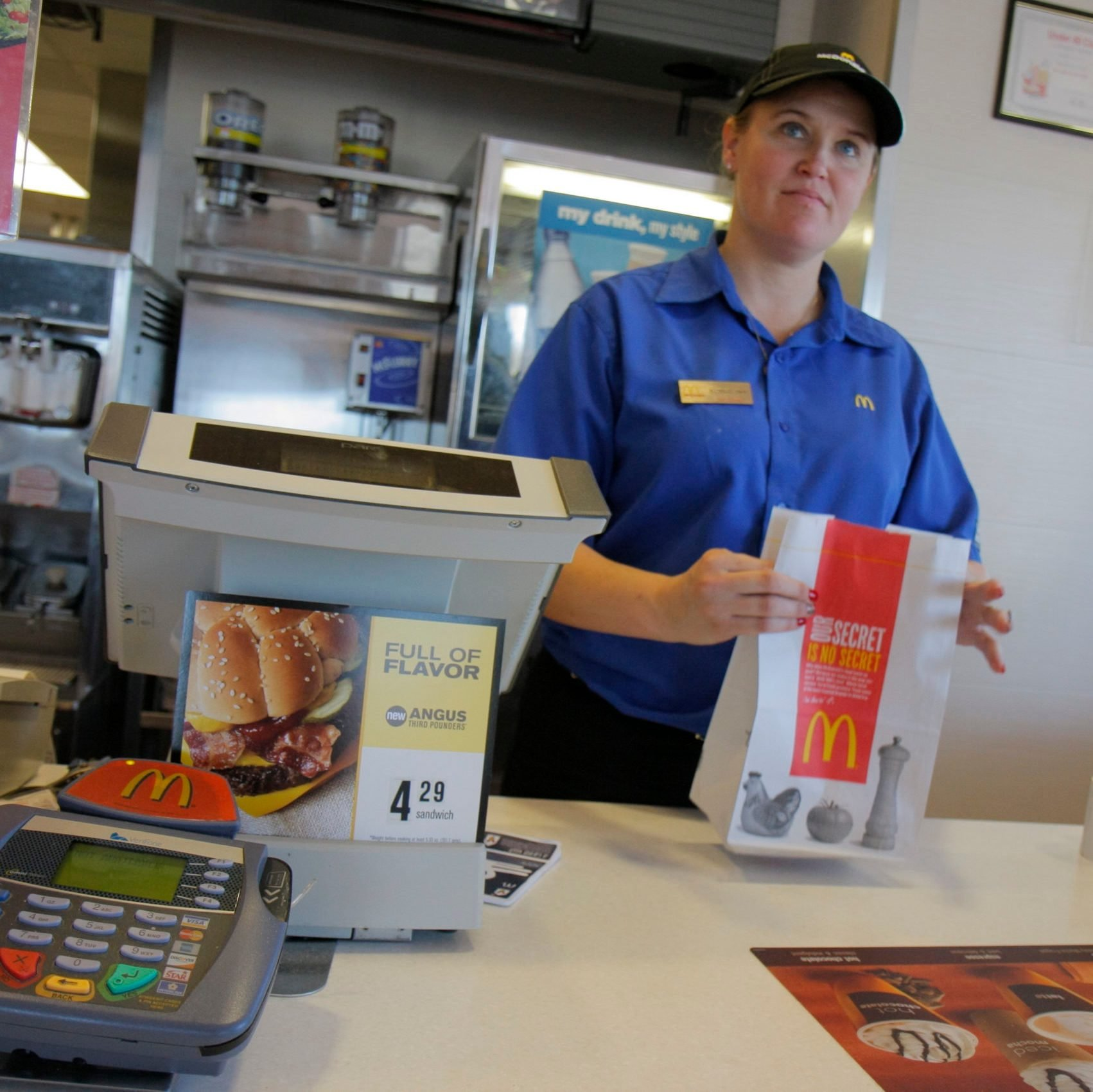 A woman cashier at the counter in McDonald's Restaurant.