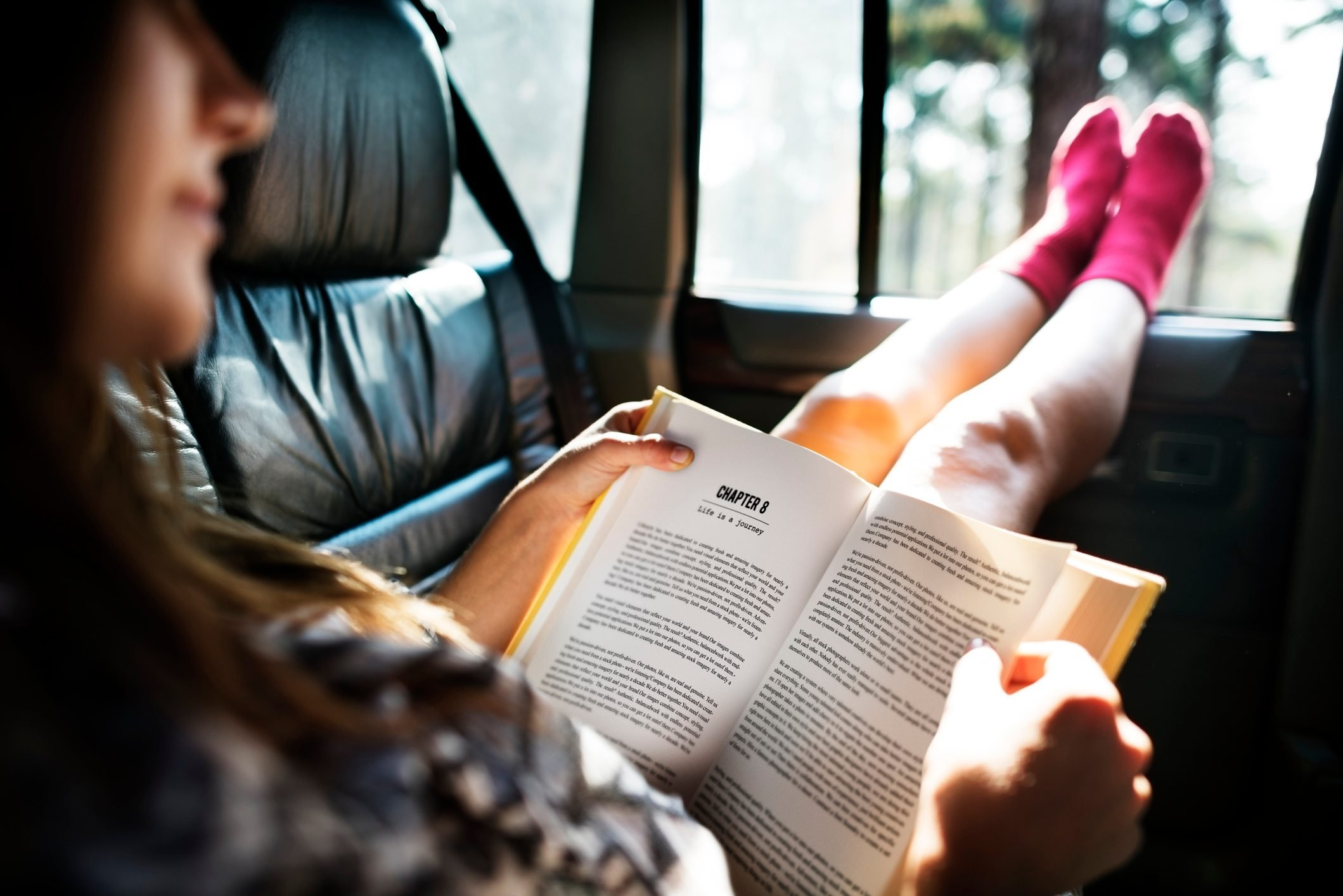 Girl Reading Book Inside Car Concept