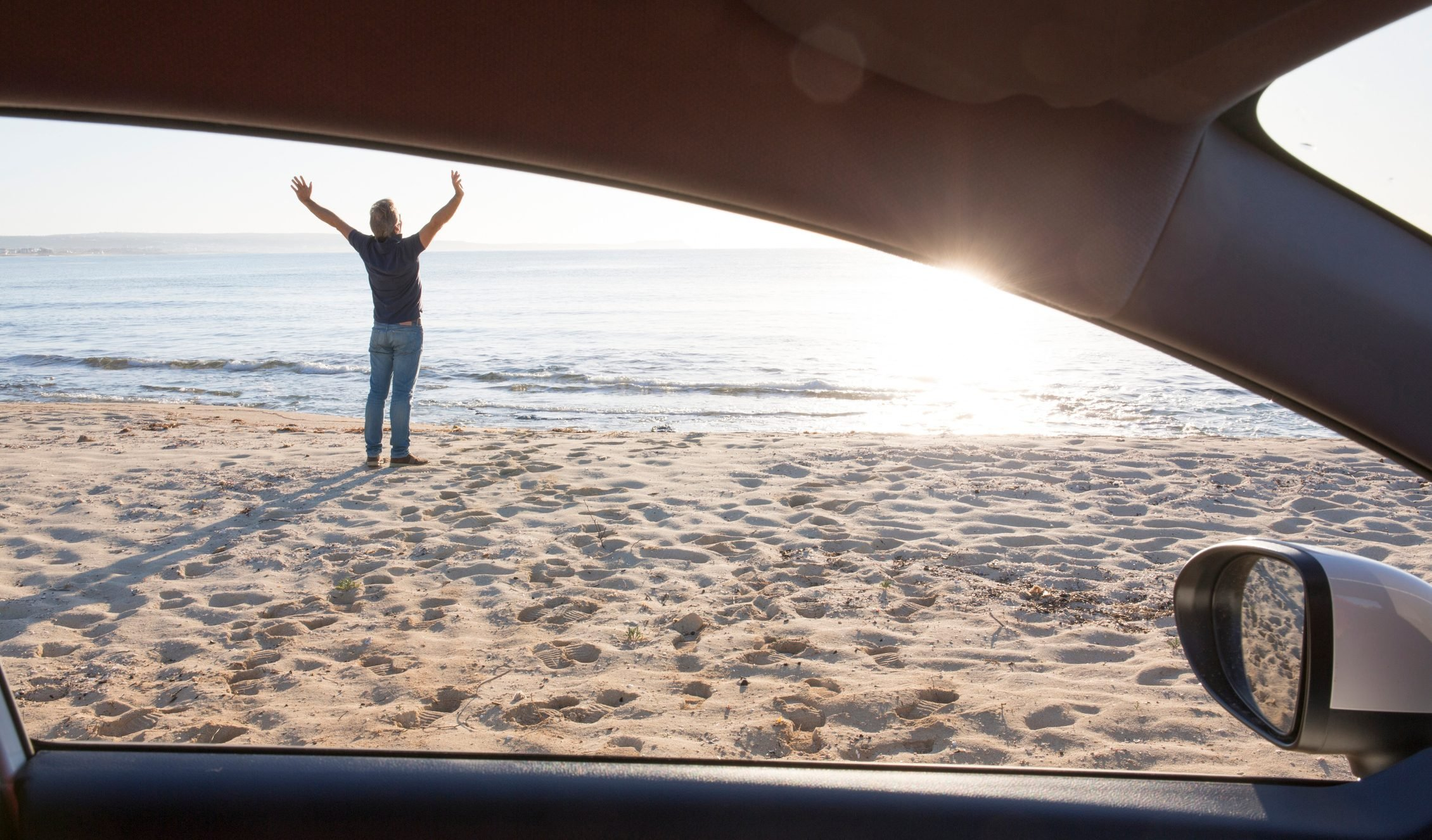 Man stretches outside car on beach, by sea shore