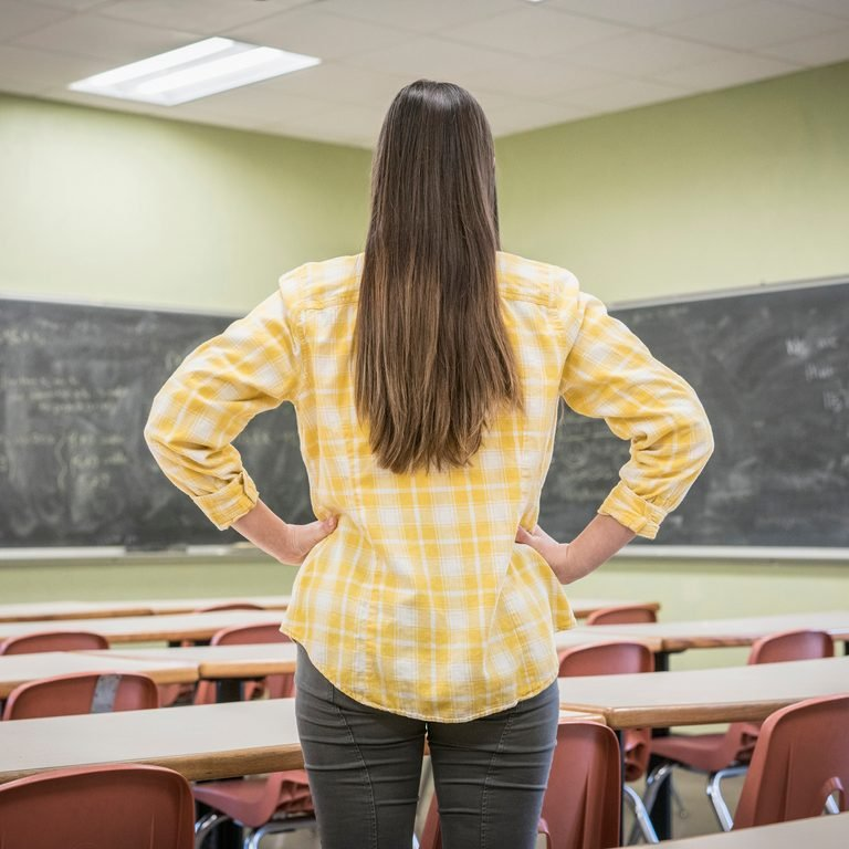 Caucasian woman standing with hands on hips in classroom