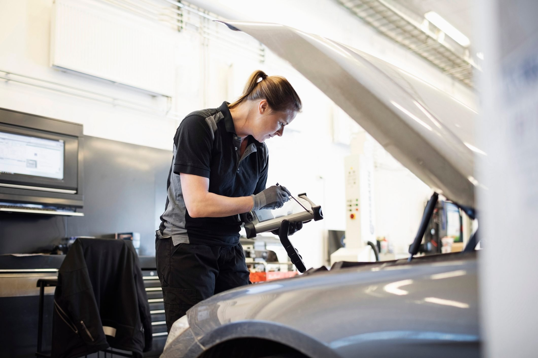 Female mechanic using technology while examining car at shop