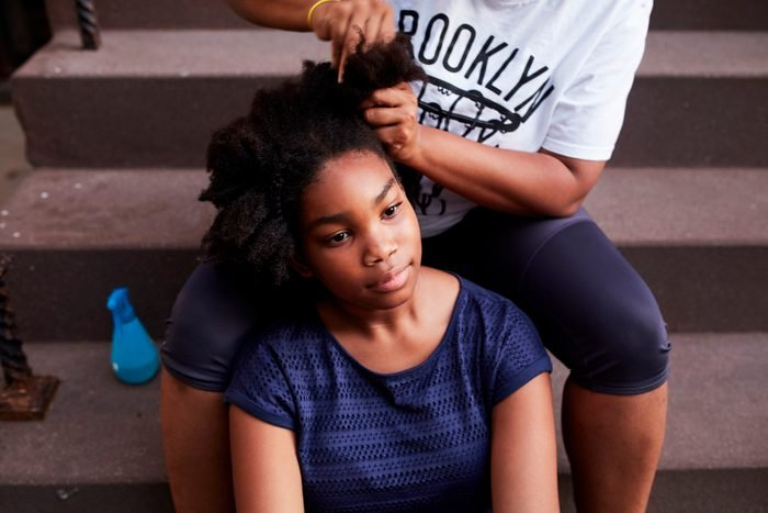 Black mother styling hair of daughter on staircase