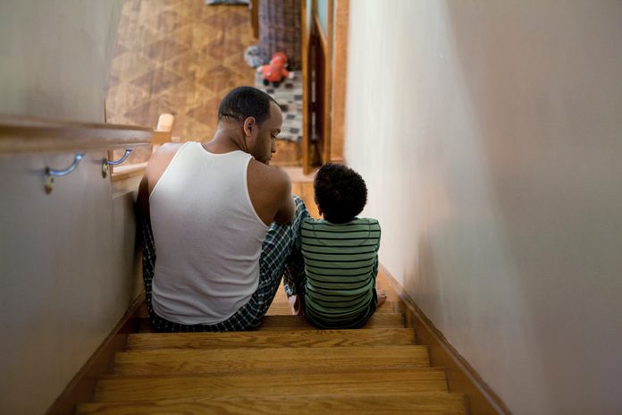 father and son having a conversation sitting on the stairs at home