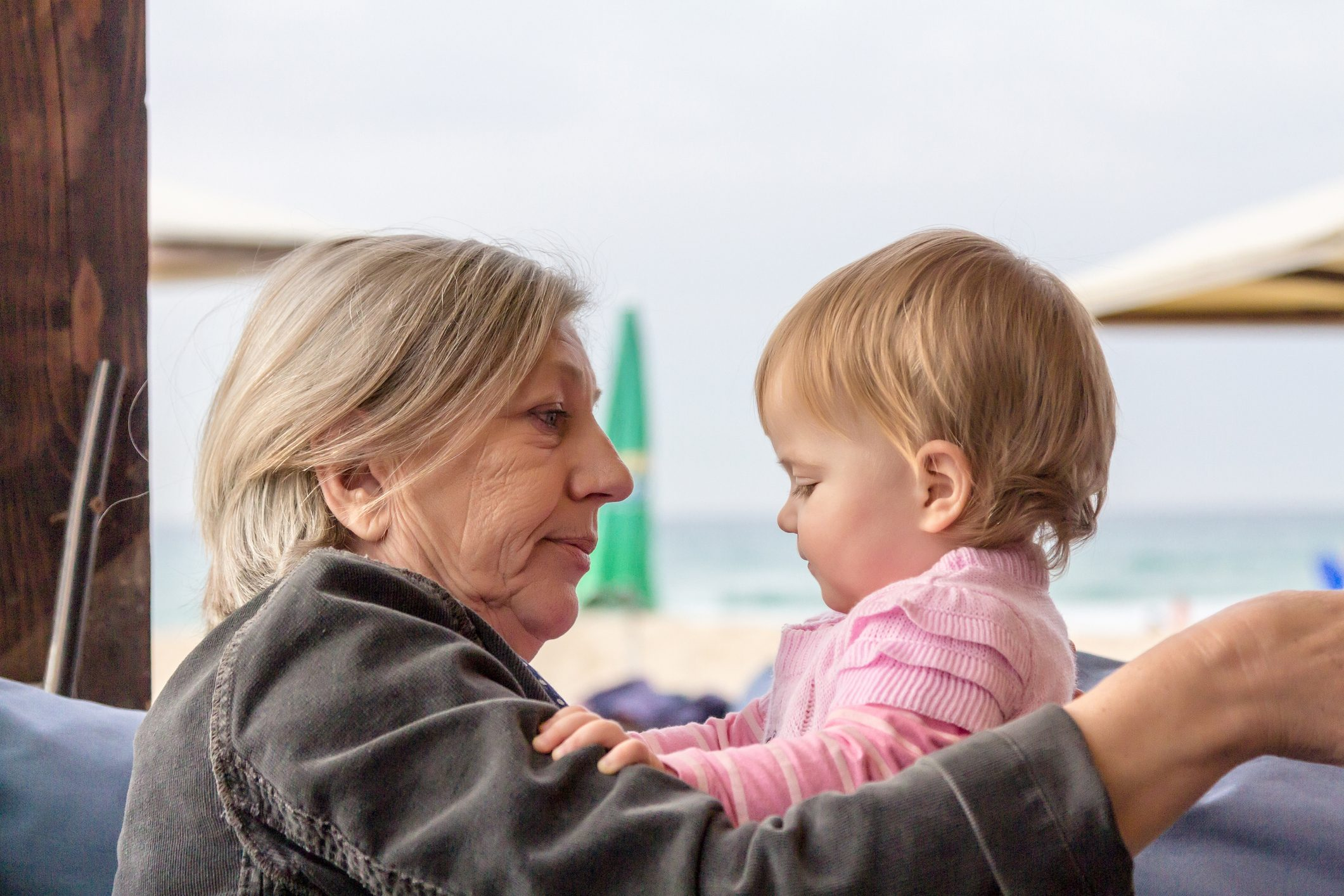 Grandmother holding and hugging her cute baby granddaughter