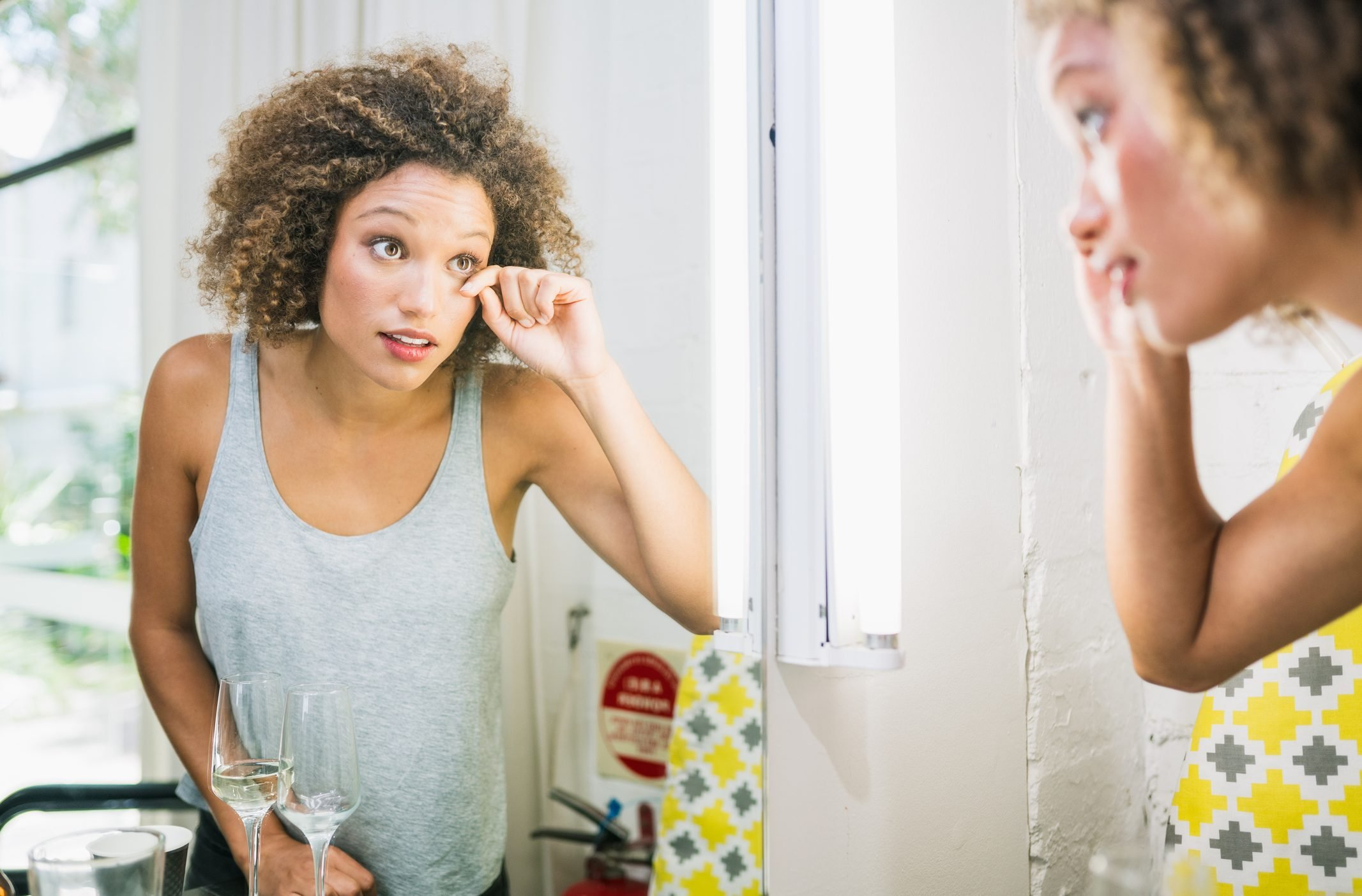 Mixed race woman doing make up in front of mirror.