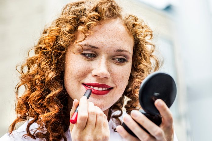 Portrait of freckled young woman applying lipstick
