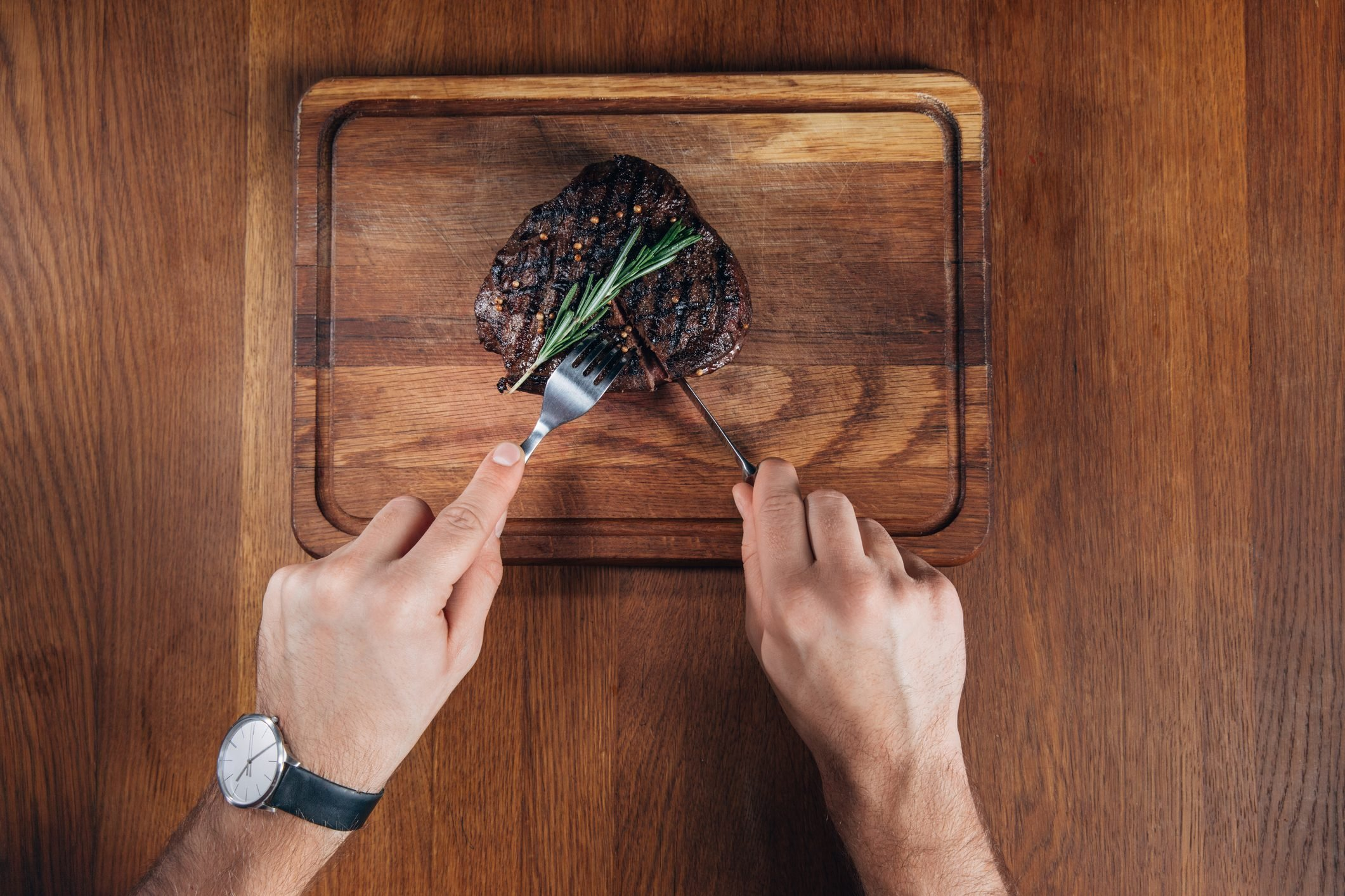 cropped shot of man cutting grilled steak on wooden board