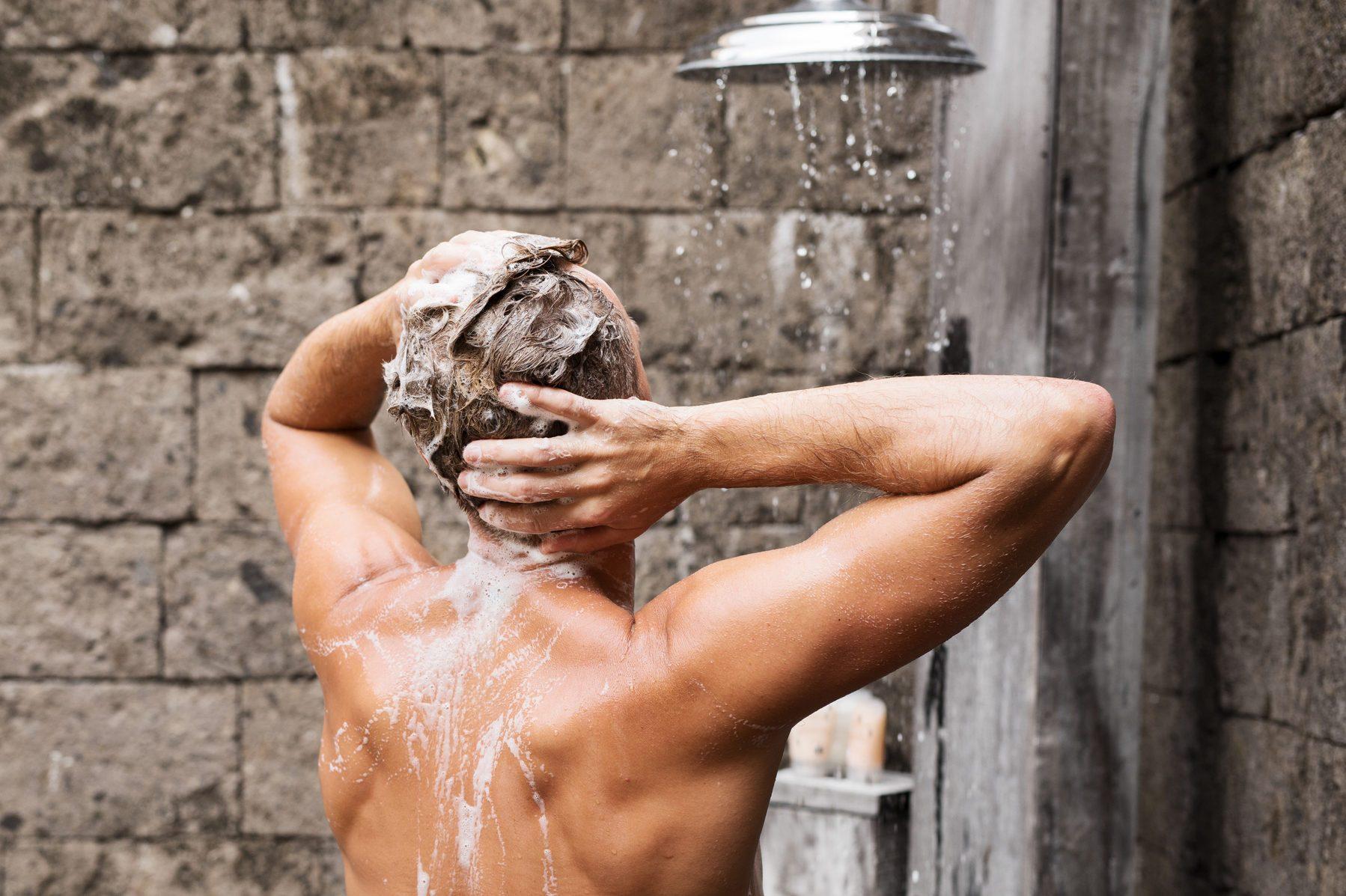 Man taking shower and washing hair