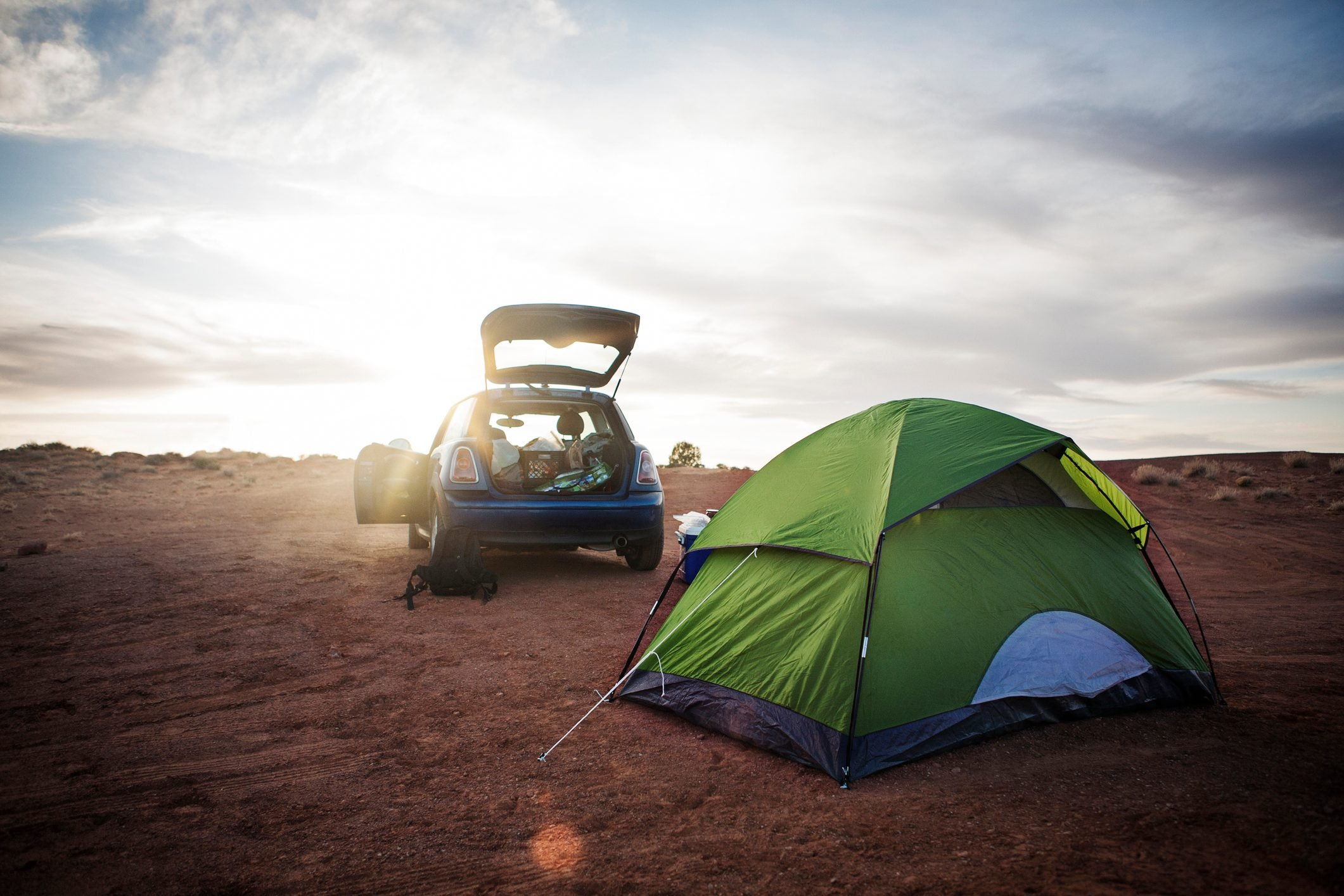 Tent and car on field against cloudy sky