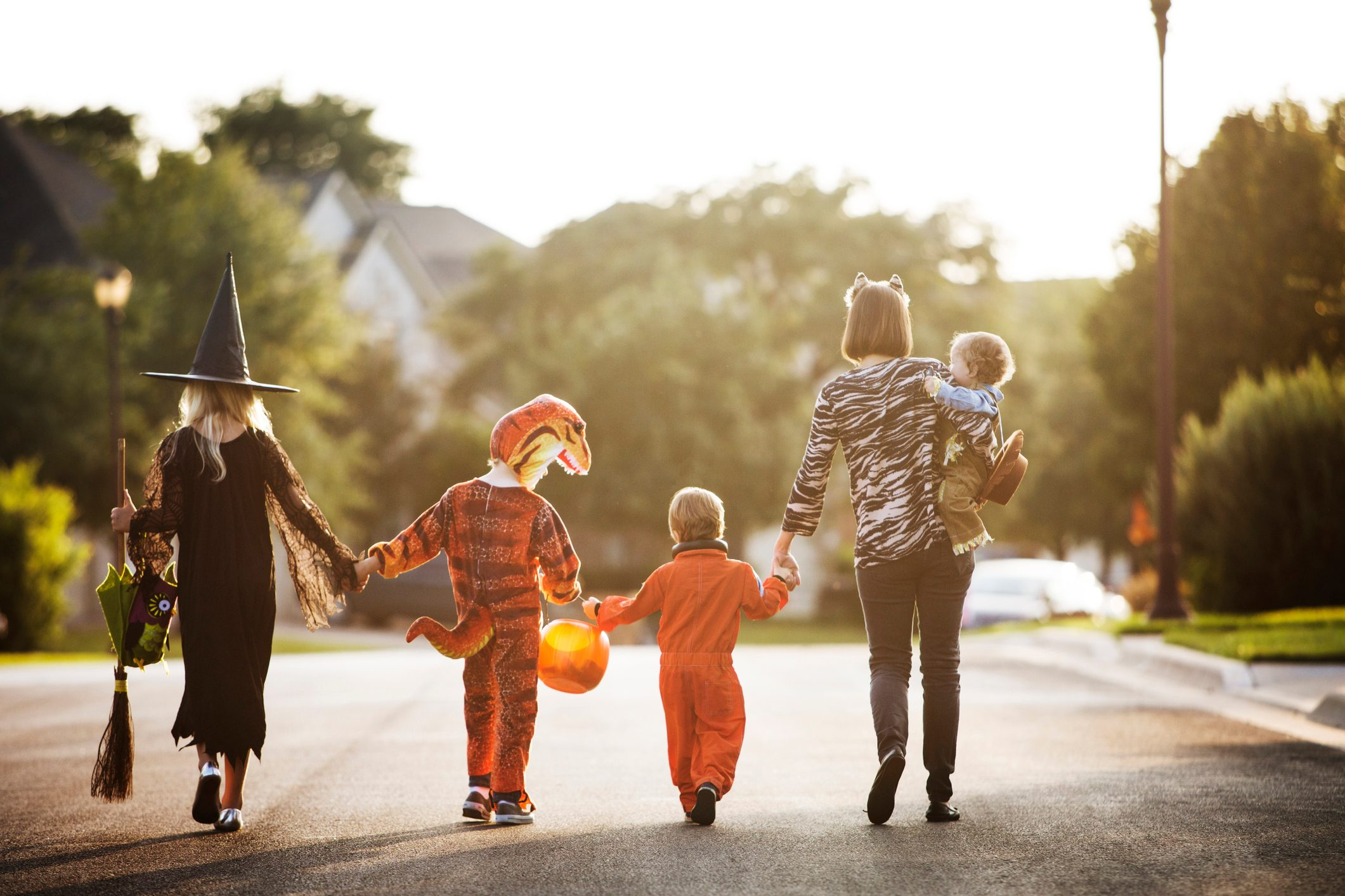 Rear view of women with children dressed for Halloween party walking on street