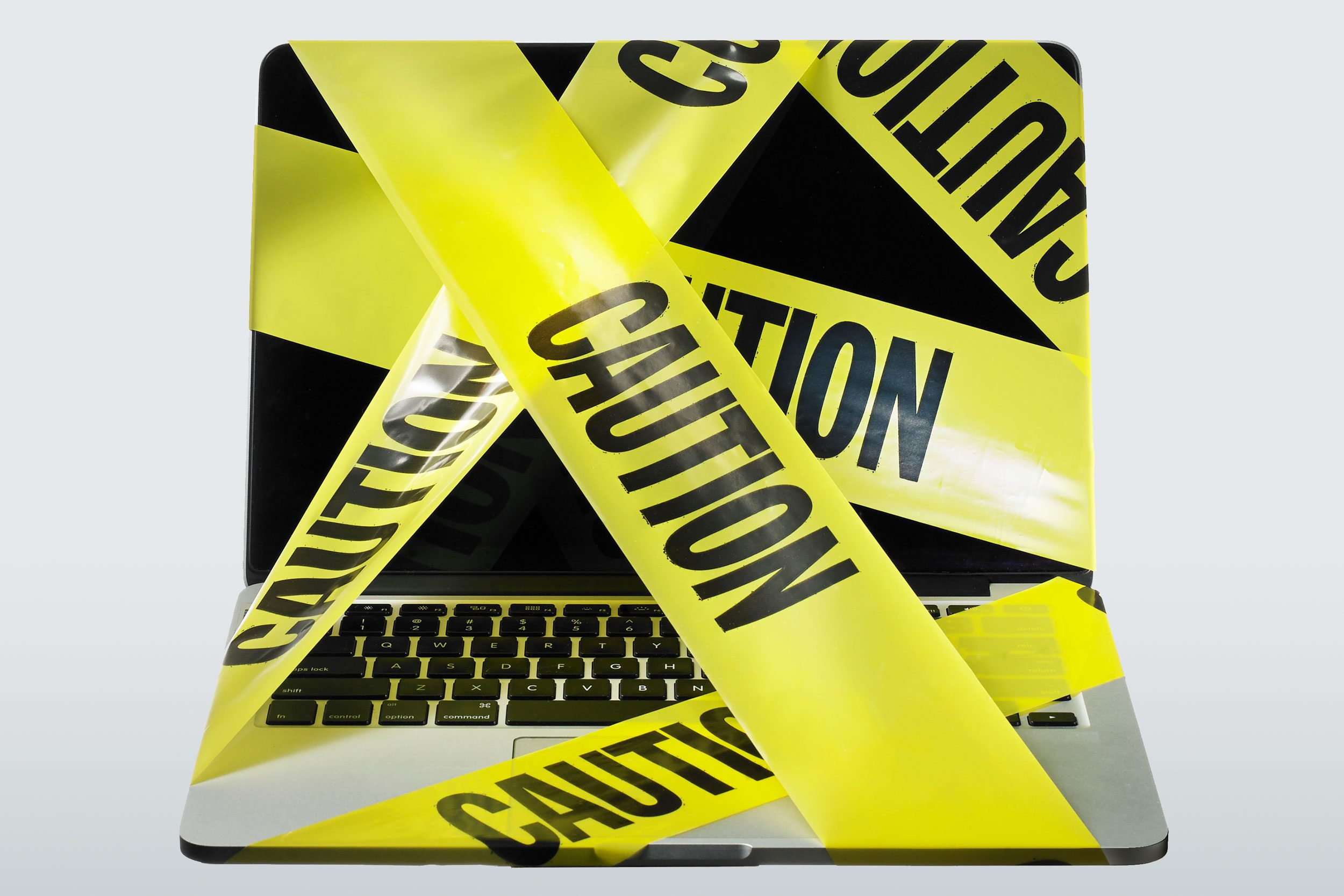 laptop computer wrapped in caution tape