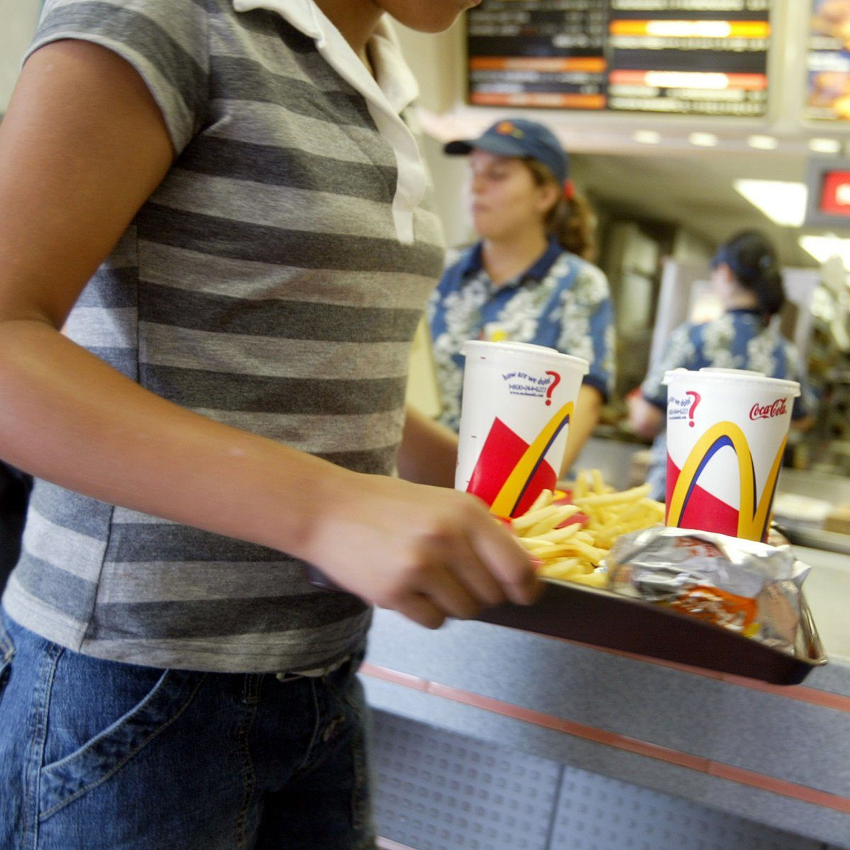 MIAMI, FL - JUNE 19: A customer carries a tray of food at McDonald's June 19, 2003 in Miami, Florida. News reports say that In response to warnings that use of antibiotics on U.S. farms is making the drugs less effective for treating people, the fast-food chain is directing some meat suppliers to stop using antibiotic growth promoters altogether and encouraging others to cut back. (Photo by Joe Raedle/Getty Images)