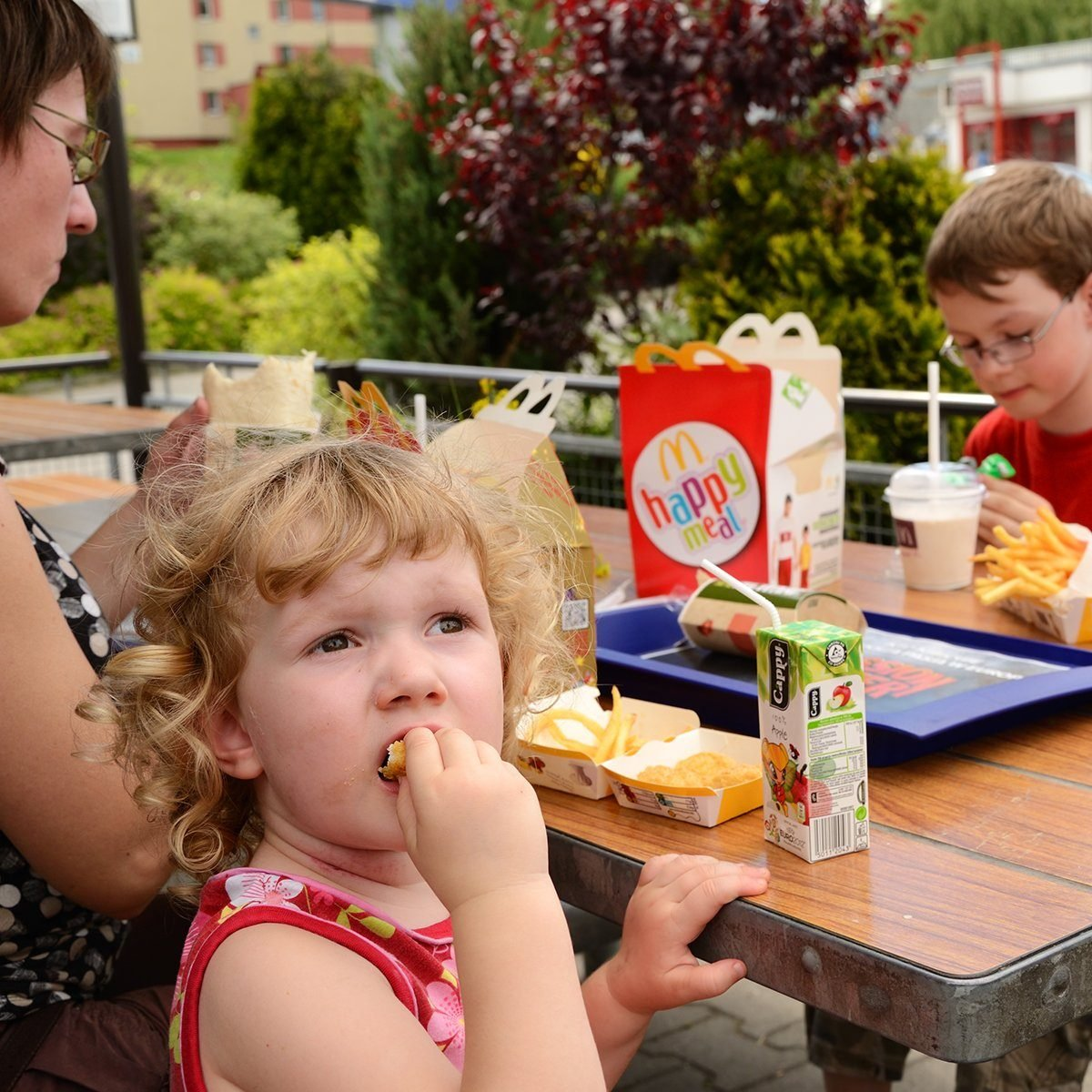 """""""Krakow, Poland - June 8th, 2012: Mother with two kids having a lunch in McDonald's, in the outdoor part of the restaurant. 3 years old blonde girl in the foreground, looking back and keeping a nugget in her mouth. Mother sitting on her left. 8 years old boy sitting opposite. Happy Meal box, some French fries, blue tray, milk shake, and a box with Cappy juice on the table."""