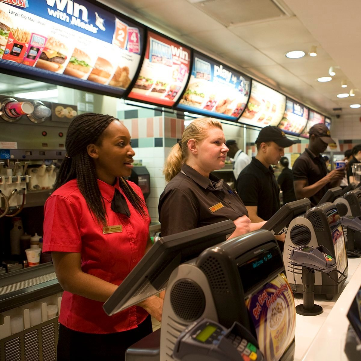 MdDonald's workers, dressed in their new more stylish uniforms take orders from customers at the new trendy coffee bar style ambience and design at the Cannon Street branch of McDonalds in the City of London. This is one of the flagship branches for this new design as the corporation takes on the process of 're-imaging' the fast food chain. This redesign, with new colours: khaki, lime, orange and russet, in a vibrant mixture of geometrics, lines and swooshes has been created for McDonald's by French Designer, Philippe Avanzi. It includes comfortable easy-chairs and stools, drop down lighting and in total, a whole new feel. This is part of a new global strategy to give McDonalds branches in different countries a uniquely local character, both in terms of the decor and some of the food served. (Photo by Gideon Mendel/Corbis via Getty Images)