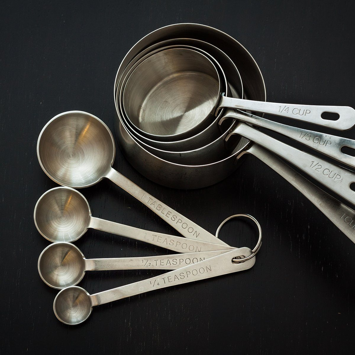 Measuring cups and spoons with a dark background.