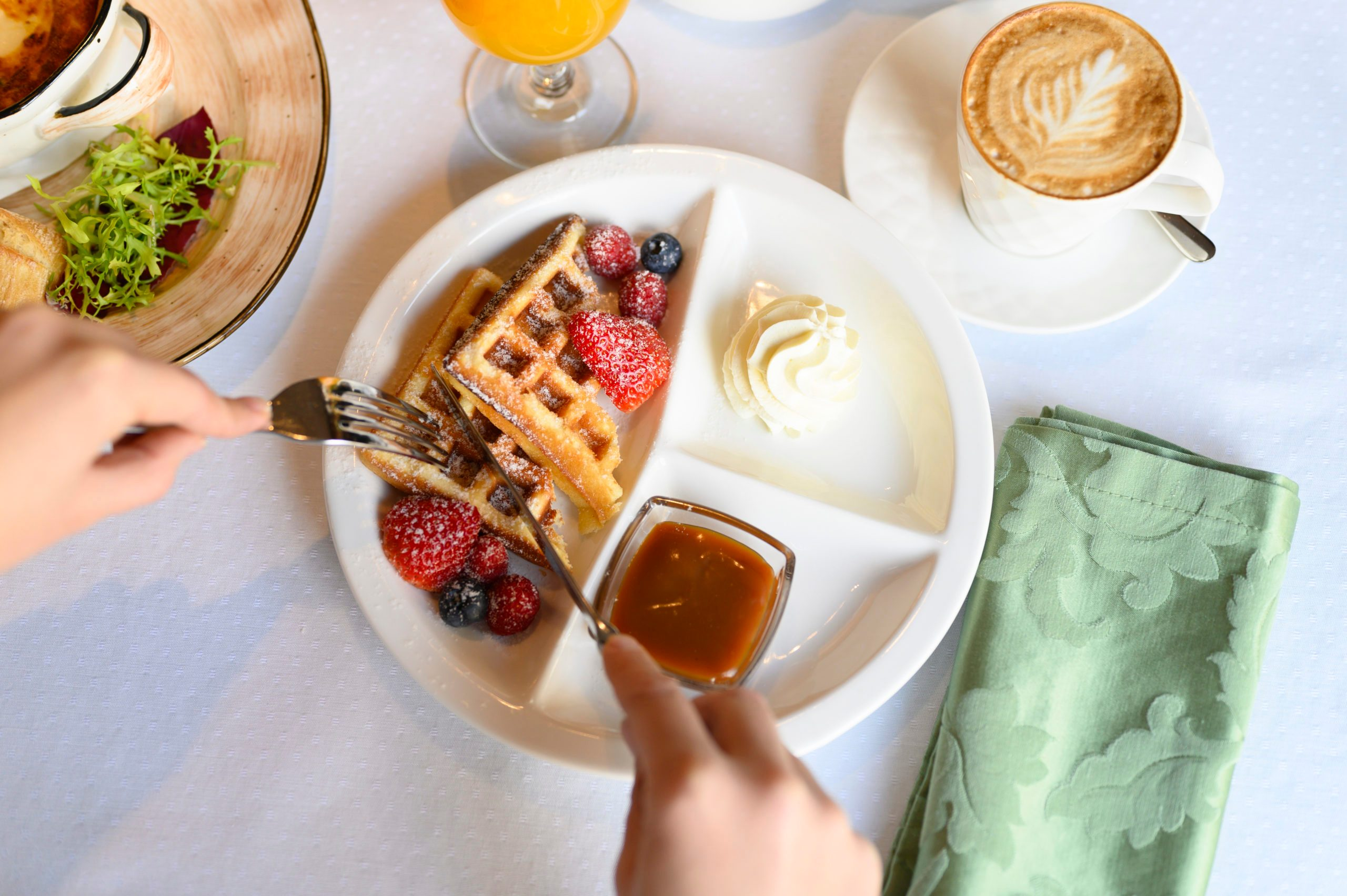 morning Breakfast or brunch in the restaurant. table with drinks and food. women's hands cut Viennese waffles with a knife and fork. selective focus