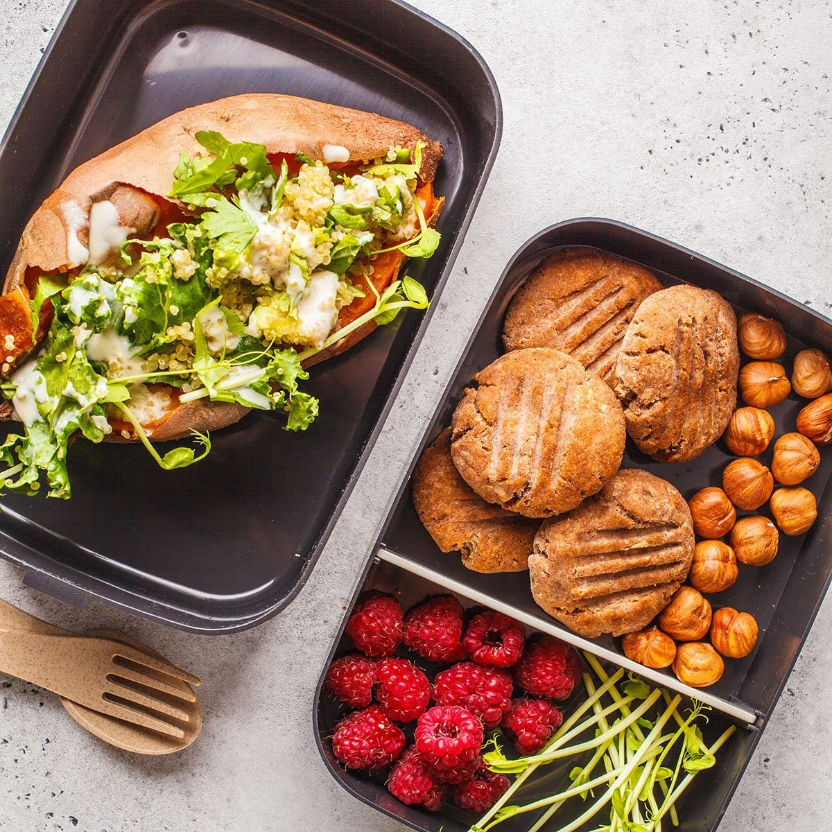 Healthy meal prep containers with quinoa Stuffed Sweet Potatoes, cookies, nuts and berries, overhead shot