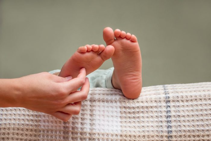 close up of hand tickling child's feet