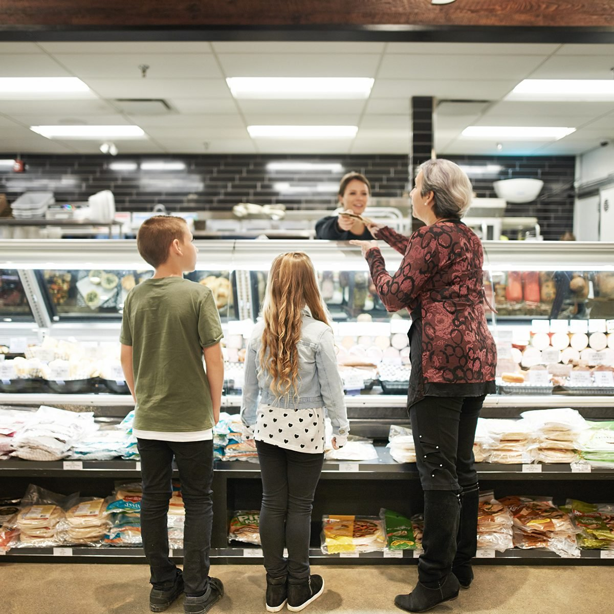 Shot of a mature woman shopping with her grandchildren at a grocery store