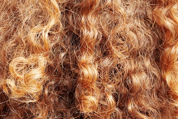 Woman's bright red locks of hair from behind
