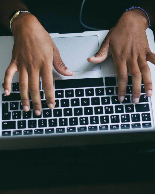 Woman's hand typing on keyboard of laptop