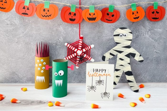 Kids Halloween Crafts arranged on a simple background; jack-o-lantern garland, toilet paper roll monsters, yarn and popsicle stick spider web, thumbprint spider card, masking tape mummy