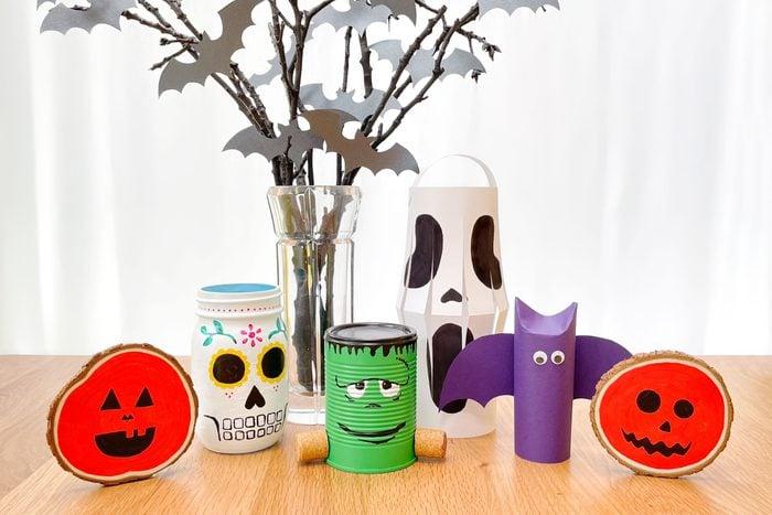cute, cheap halloween decorations on a wooden table with white background; pumpkin wood slices, mason jar sugar skull, spooky centerpiece, tin can frankenstein, paper scream lantern, paper bat