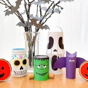 cute, cheap, DIY halloween decorations on a wooden table with white background; pumpkin wood slices, mason jar sugar skull, spooky centerpiece, tin can frankenstein, paper scream lantern, paper bat