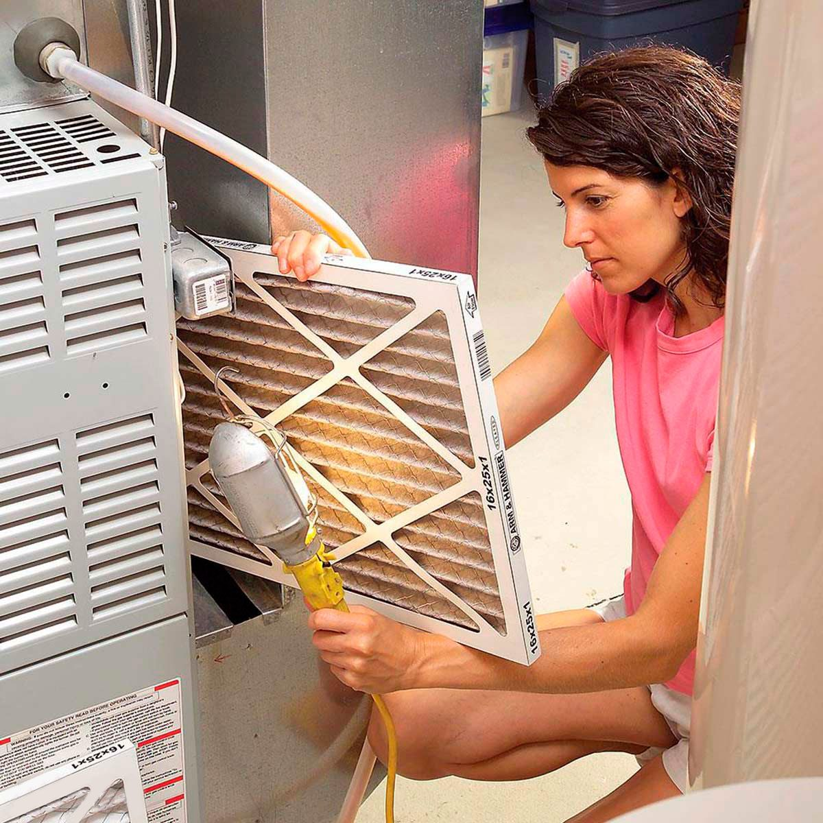 woman checking furnace filter