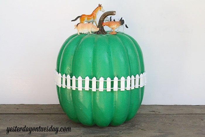 pumpkin painted green with a miniature white picket fence around it; plastic farm animals added on top