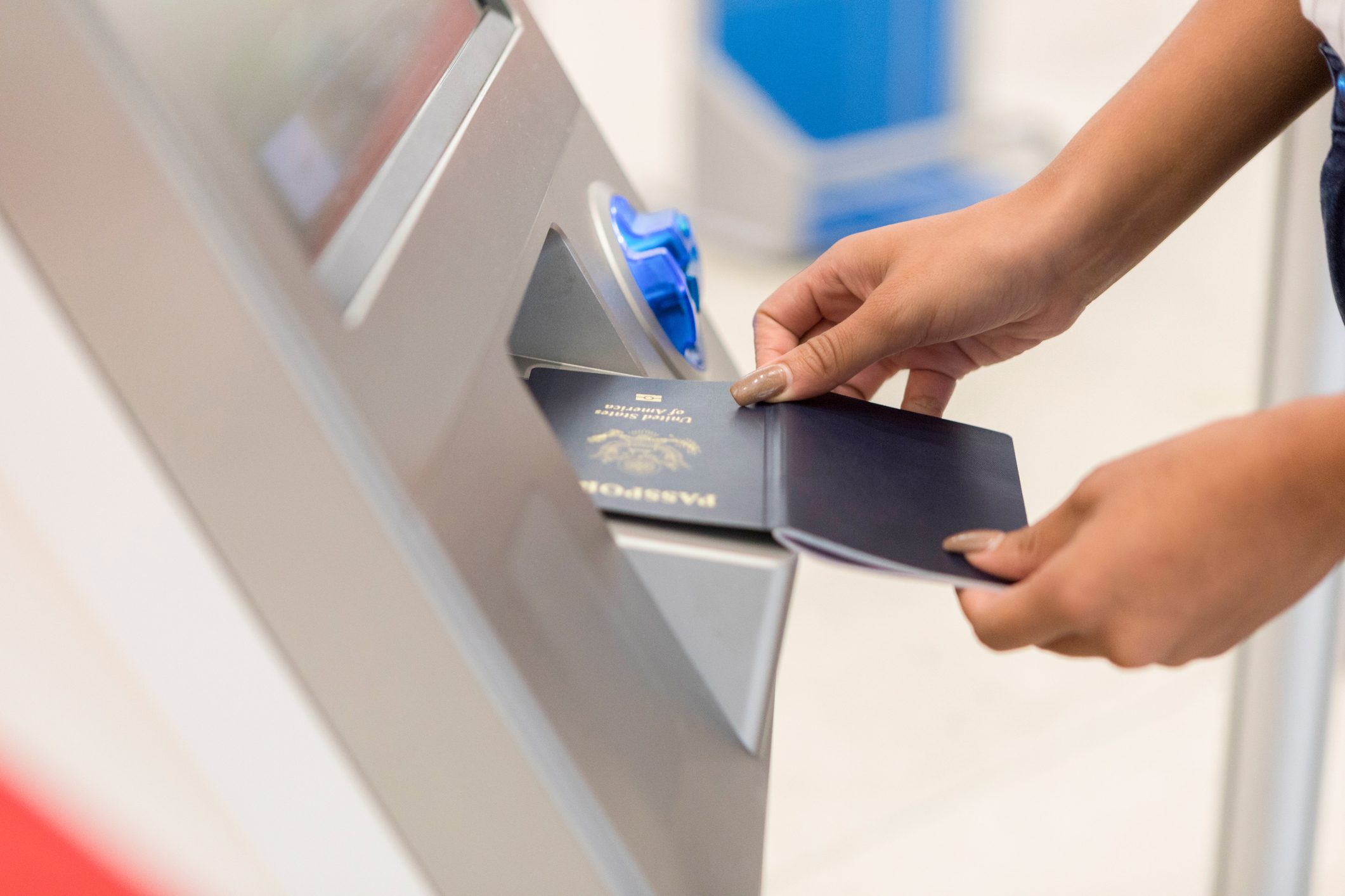 Unrecognizable woman scans passport at airport kiosk