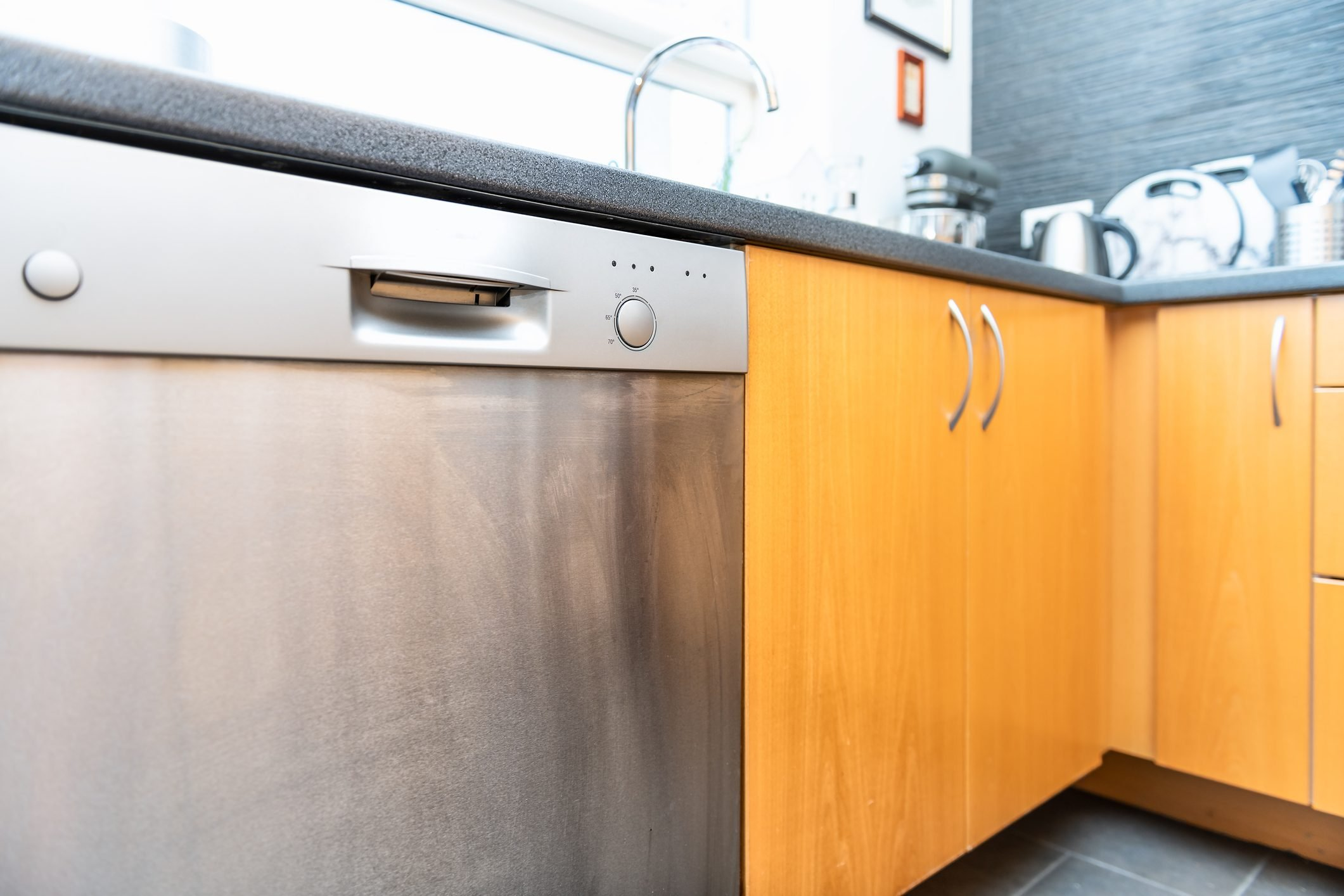Closeup of side of modern wood, wooden finish kitchen drawers with steel handles, cabinets, dishwasher, tile, tiled brown, yellow floor, utensils, faucet