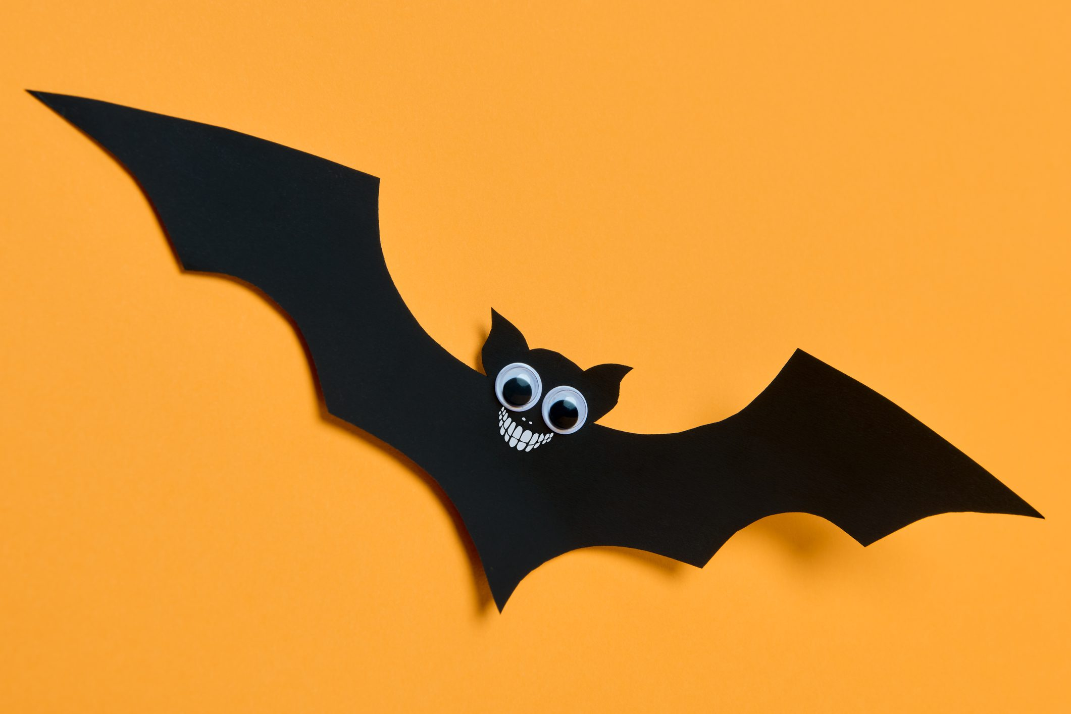 Halloween decoration concept. Cute smiling black paper bat flying over orange background. Halloween background.