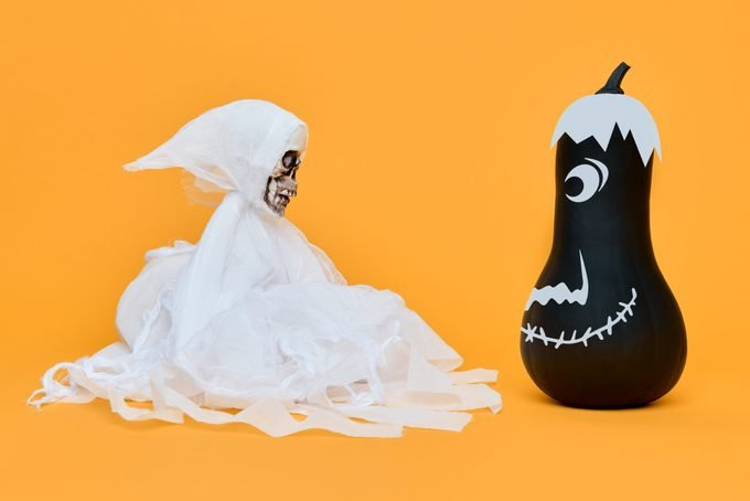 Spooky Halloween Concept. Scary skeleton face to face with cute smiling pumpkin. Funny Halloween Background.