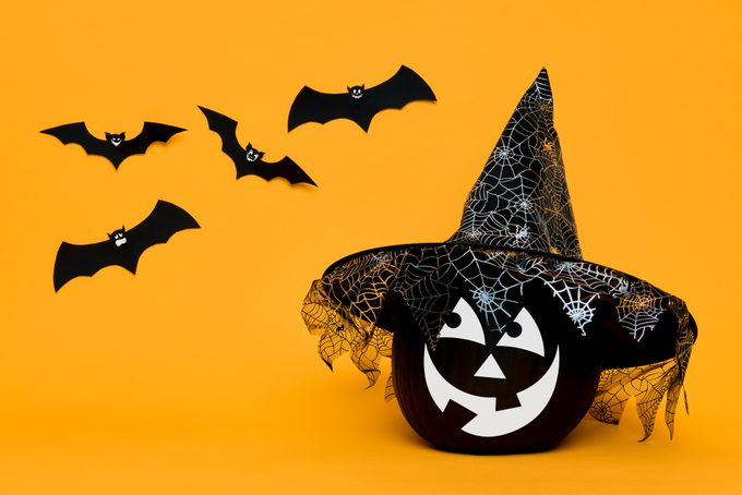 Large Black Halloween Pumpkin with cute smiling face wearing witch hat looking at flying paper bats over orange background.