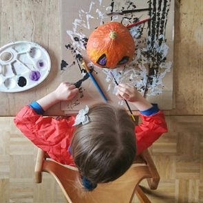 Child painting pumpkin with halloween colors