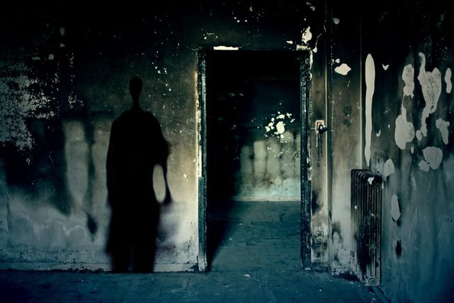 Scary scene with spooky shadow in a dark room of an abandoned building