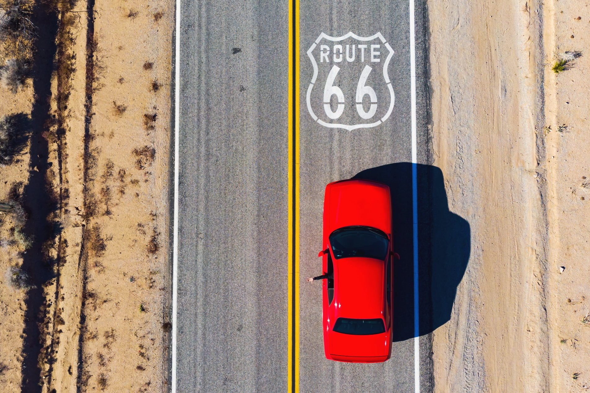 Drone view of American car driving in a straight road of the famous Route 66.