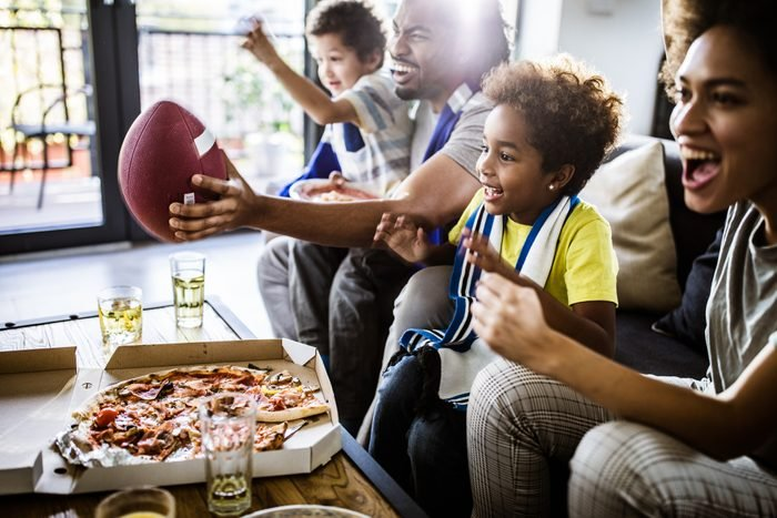 Cheerful black family cheering while watching rugby match on TV at home.