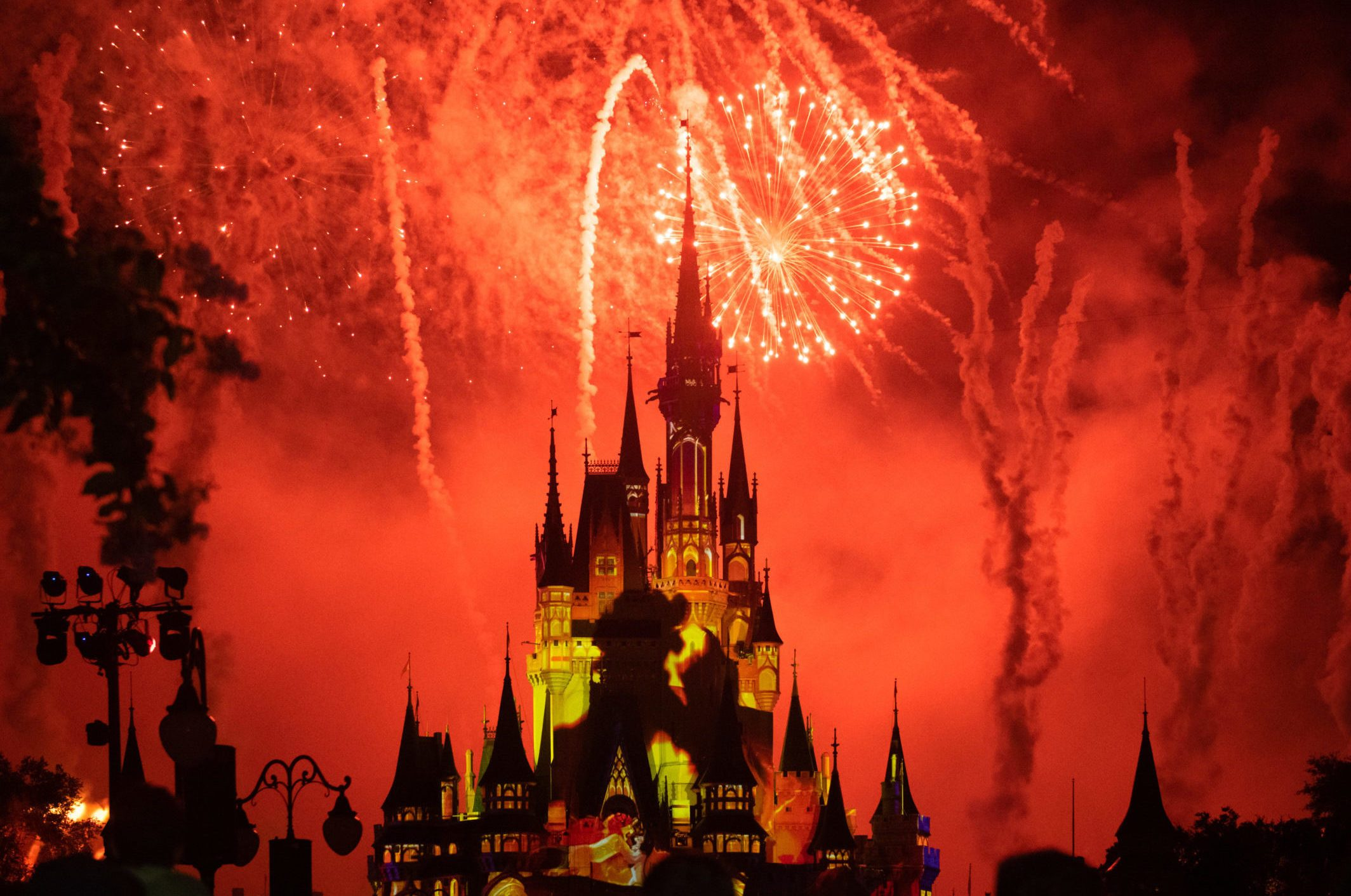 Red fireworks and yellow strobe lights illuminating the...