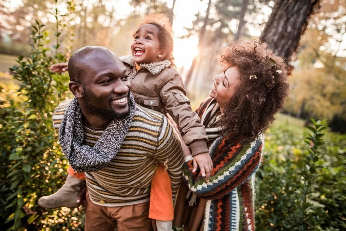 Happy black parents having fun with their daughter at the park.